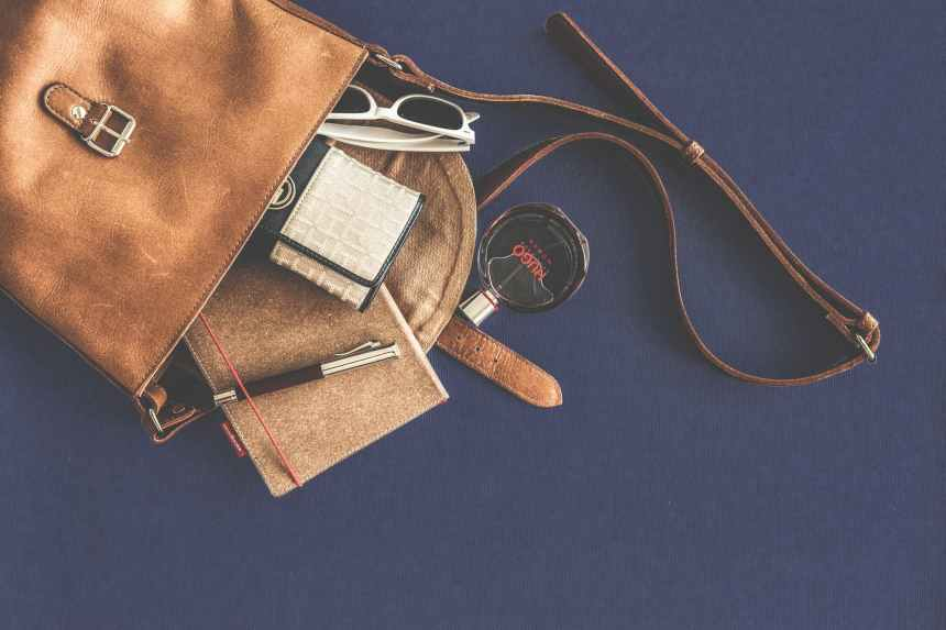 brown leather crossbody bag with white framed sunglasses